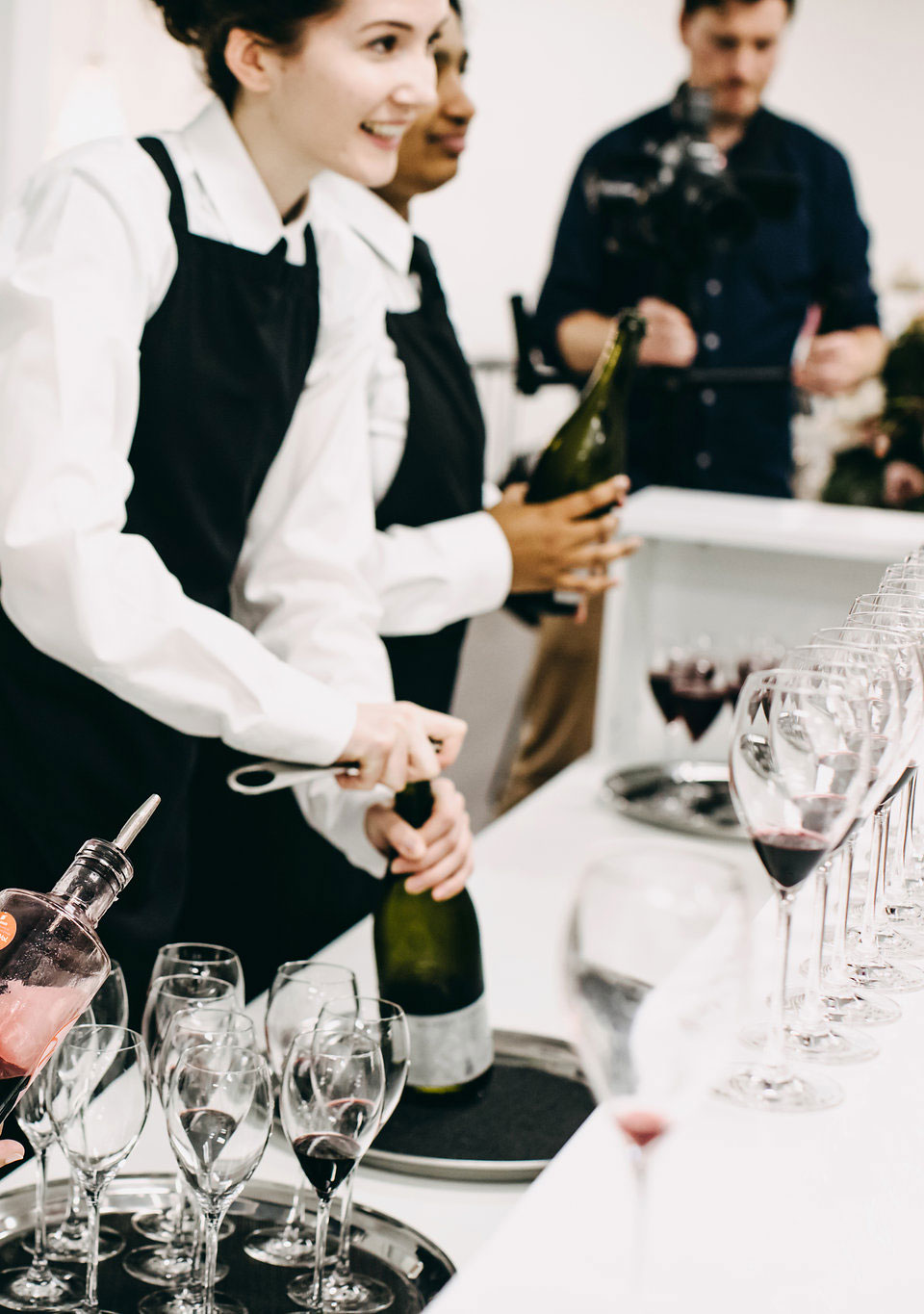 Caterer opening a bottle of wine at an event